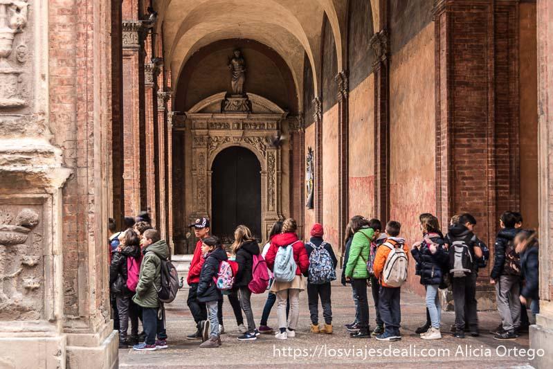 fila de escolares debajo de un pórtico esperando para subir a la torre