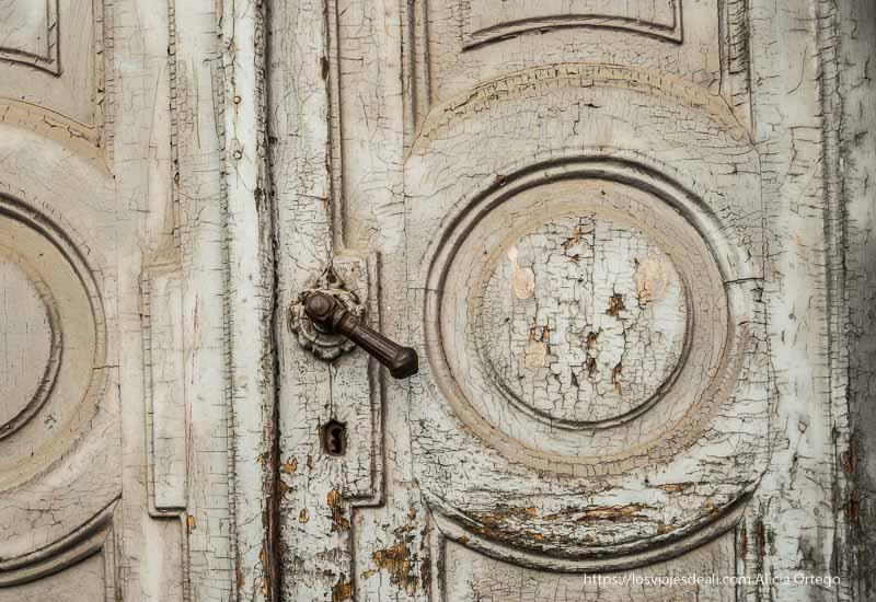 pomo de hierro de una puerta de madera con pintura ajada y cuarterones circulares