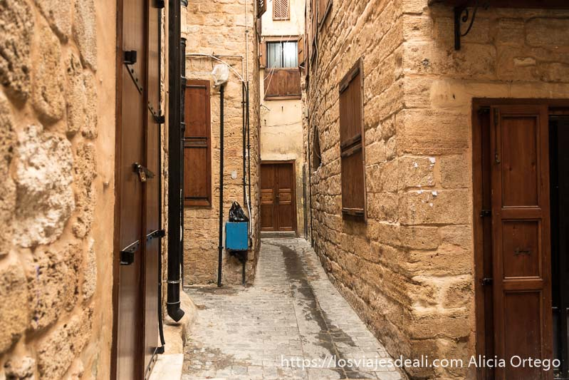 calle estrecha con edificios de piedra y ventanas y puertas de madera