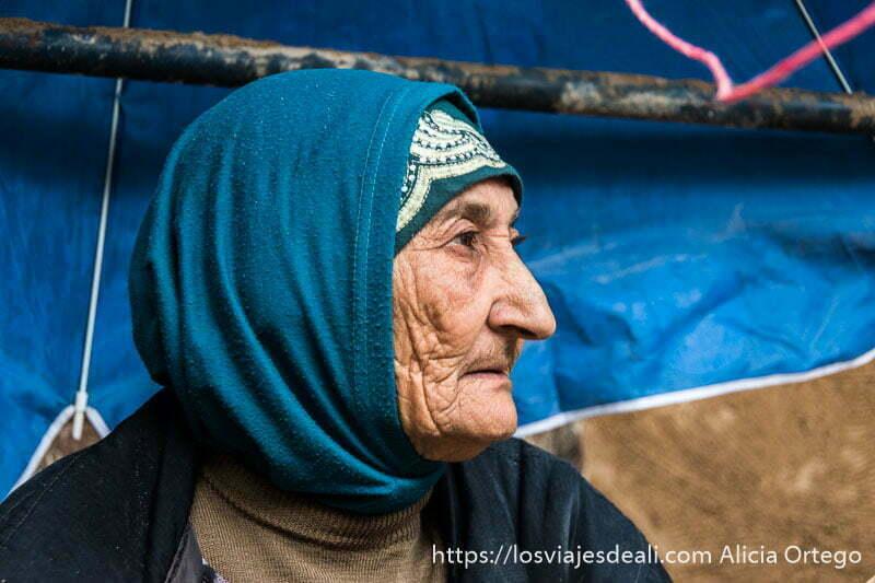 anciana de perfil con pañuelo azul cubriendo la cabeza