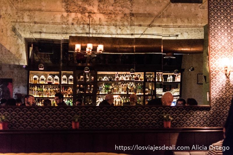 interior de un bar de beirut con gran espejo donde se refleja la barra llena de botellas y la gente