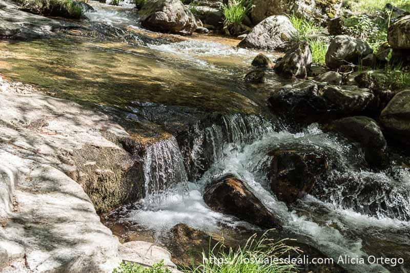 rápidos de agua entre rocas en el arroyo en la ruta de 1 día en el valle del lozoya