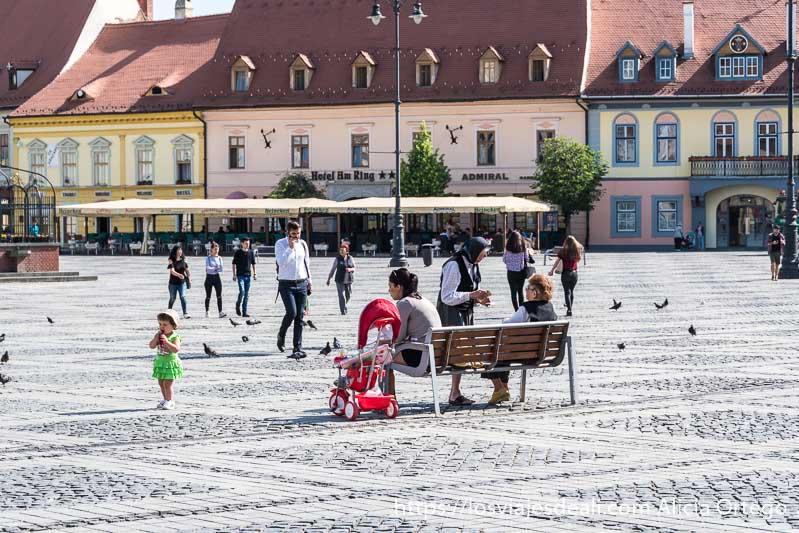 señoras sentadas en la plaza mayor de sibiu y una niña pequeña entre las palomas