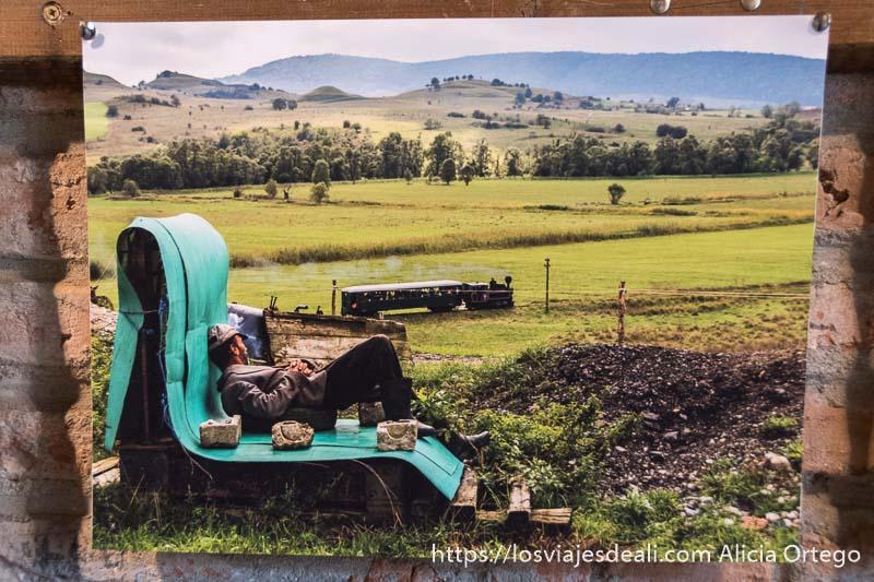 foto de campesino tumbado viendo pasar un tren de vapor en el campo rumano