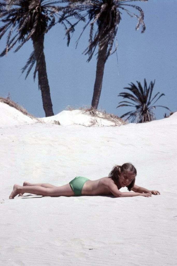 mi hermana rodando en una duna de arena blanca con dos palmeras al fondo