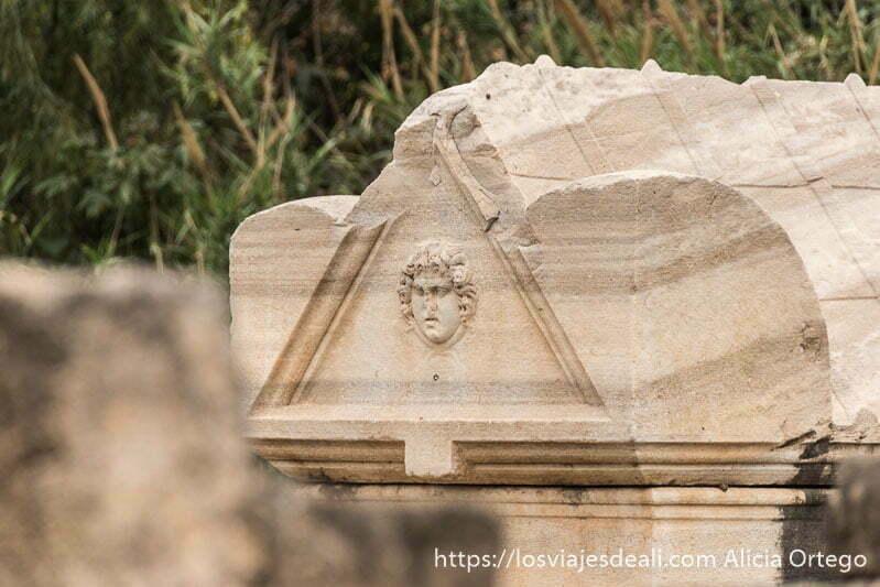 sarcófago de mármol con relieve de rostro con pelo rizado en las ruinas de tiro
