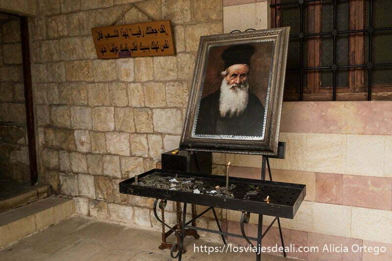 cuadro con imagen de un cura ortodoxo y soporte para velas en una iglesia de deir el qamar en la excursión a los alrededores de beirut