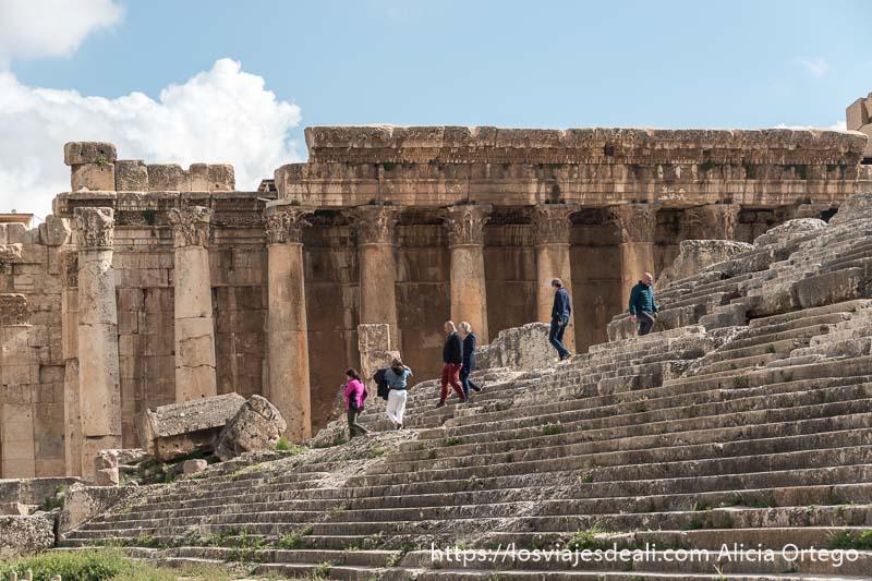 escalinata de piedra por donde varias personas suben y bajan al templo de júpiter y al fondo las columnas del templo de baco