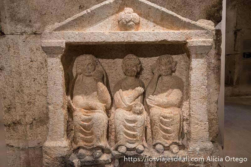 sarcófago romano con tres figuras en relieve muy realistas de una mujer y dos hombres sentados con sus togas