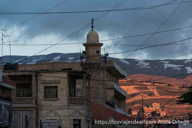 minarete de mezquita con cables alrededor y montañas detrás enrojecidas con luz de atardecer en baalbek en valle de bekaa