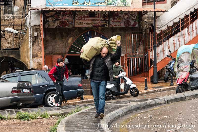 hombre llevando saco en el hombro andando por una calle de trípoli