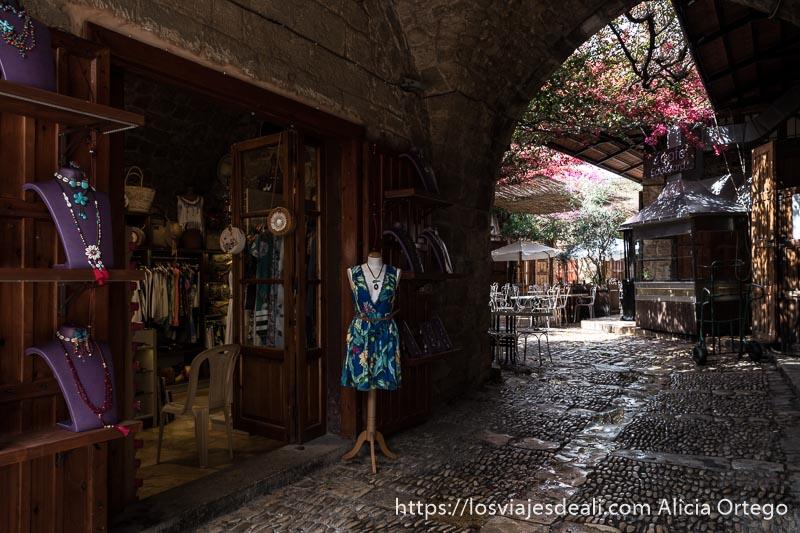 tienda de joyas y ropa en calle empedrada que da a un patio con mesas y sillas en byblos