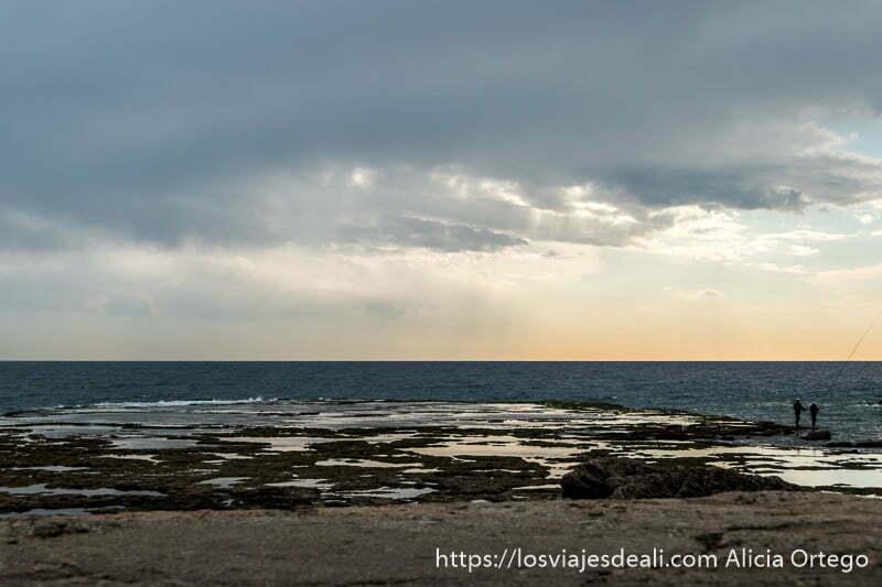 plataforma de roca frente al mar con luces de atardecer una gran nube y dos pescadores con sus cañas a la derecha