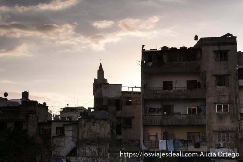 edificios medio en ruinas y minarete de mezquita con cielo de atardecer en trípoli