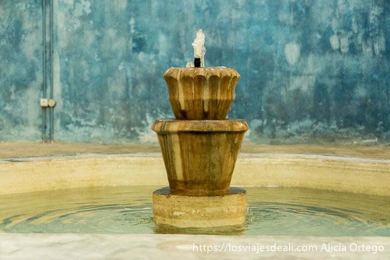 fuente con chorrito de agua en el centro de un hamman de trípoli con paredes pintadas de azul y verde