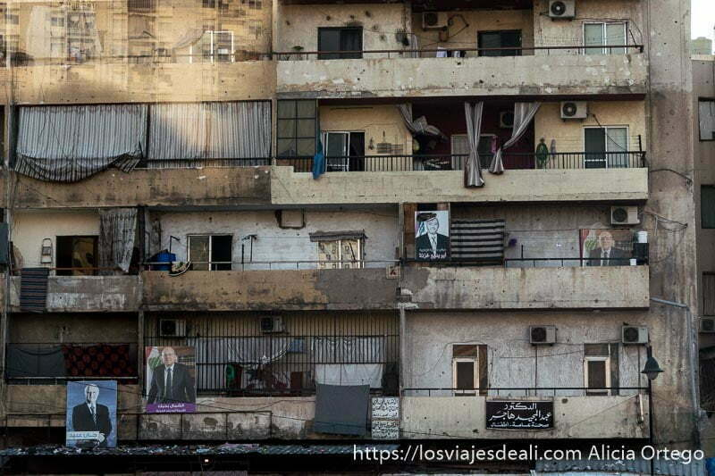 fachada de pisos con carteles de candidatos a las elecciones y toldos a rayas en Trípoli