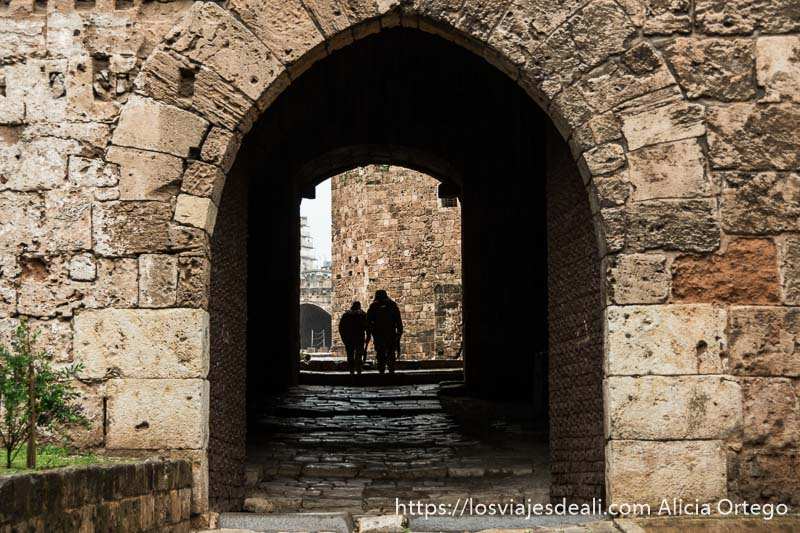 entrada al castillo de trípoli con puerta con gran arco y dos soldados recortados contra la luz