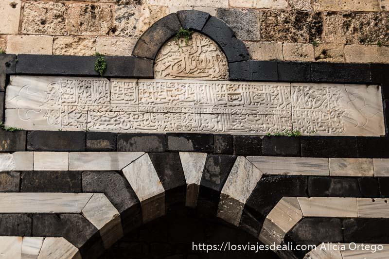 inscripción en árabe en piedra de mármol blanco rodeada de marco negro en la puerta del castillo de trípoli
