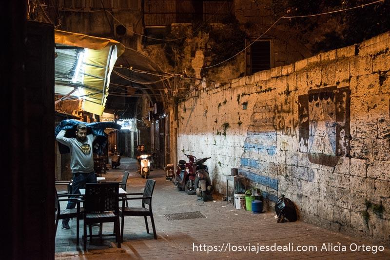calle del puerto viejo de trípoli con chico saliendo de un bar y moto viniendo desde el fondo de la calle