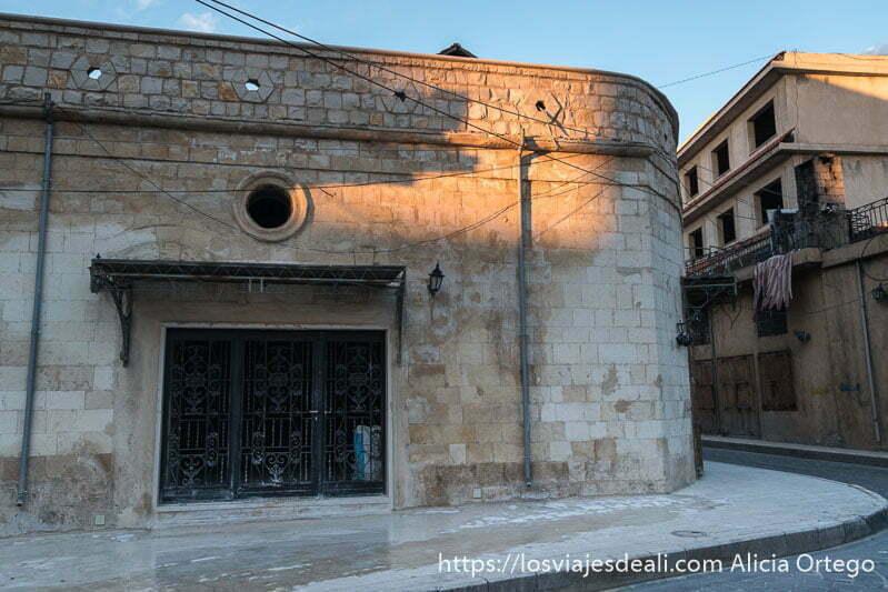 calle de la antigua baalbek con edificio de esquina redondeada iluminado por sol de atardecer