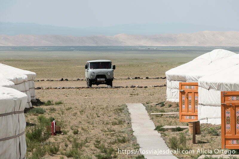 furgoneta gris de los años 70 aparcada junto a una fila de gers en nuestro campsite y al fondo la barrera de dunas del gobi en el viaje a mongolia