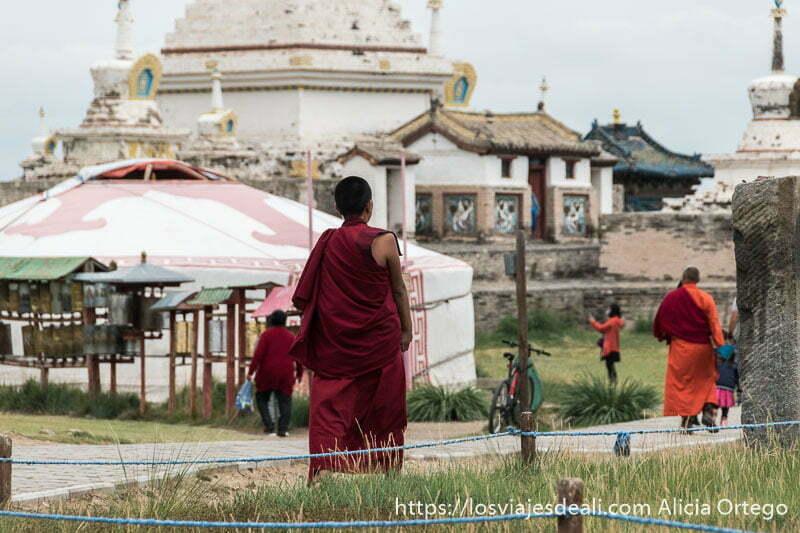 monjes budistas vestidos de rojo andando junto a los templos de jarjorin