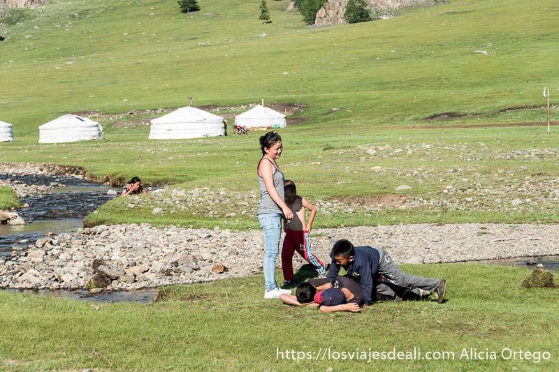 grupo de niños jugando junto al río y al fondo su campamento de gers en paisaje verde en el viaje a mongolia