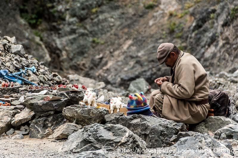 artesano trabajando en el cañón de yol am sobre unas rocas rodeado de souvenirs como pequeños camellos de lana