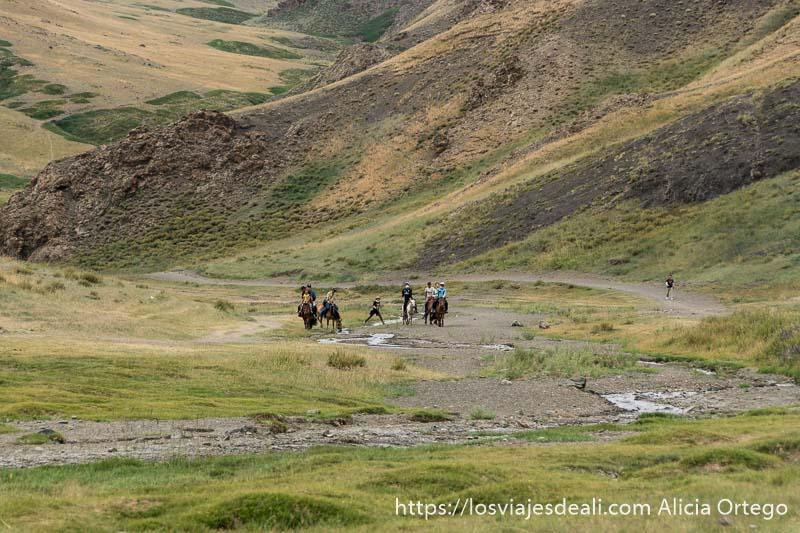 personas montando a caballo junto al río yol en la entrada al cañón en el desierto del gobi