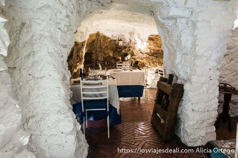 sala de restaurante cueva con piedra de paredes pintadas de blanco