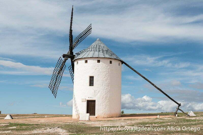 molino de viento blanco con aspas negras sobre cielo azul con algunas nubes blancas en la experiencia en la vendimia