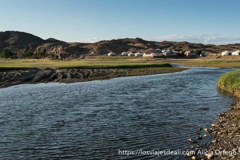 río ongii con praderas a los lados y montañas al fondo y las tiendas del campamento turístico
