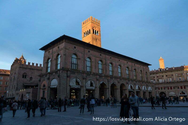 edificio del ayuntamiento con torre iluminada por sol de atardecer y al fondo torre asinelli también dorada imprescindibles de bolonia