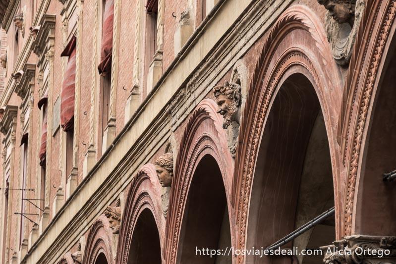 fachada de palacio con arcos y caras esculpidas entre las que está la del diablo sonriente imprescindibles de bolonia