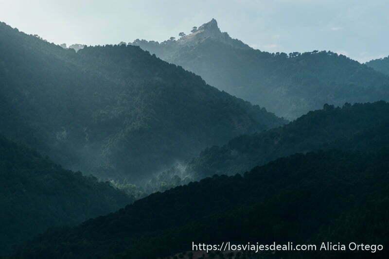 paisaje de montañas en varios niveles llenas de bosque y rayos de sol iluminando la zona central