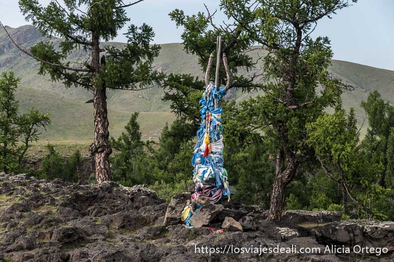 figura totem hecha con troncos y cubierta de pañuelos de seda de color azul con árboles detrás tipo abetos en el valle de orkhon