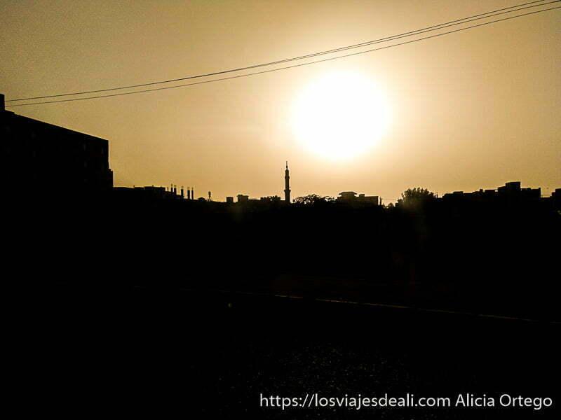 puesta de sol de jartum con minarete de mezquita recortándose a contraluz y edificios con tejados planos