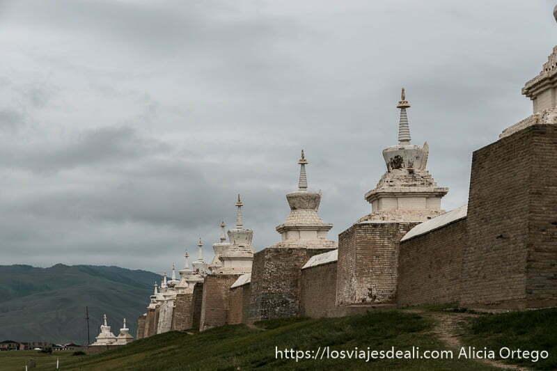 murallas de karakorum con estupas pintadas de blanco y hierba alrededor
