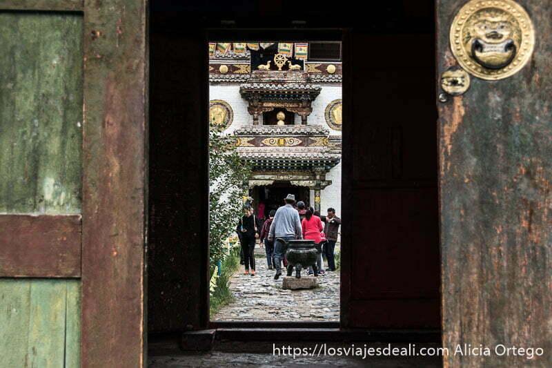 vista del patio de un templo enmarcada en la puerta del exterior con peregrinos avanzando hacia la capilla principal en karakorum
