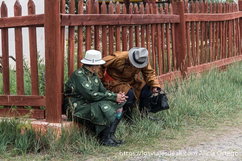 dos peregrinos mongoles con sus trajes de seda verde y marrón sentados junto a una valla de madera en karakorum