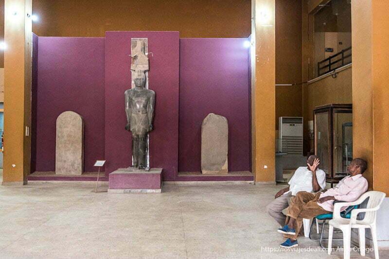 entrada al museo nacional de jartum con estatua de granito negro de faraón y dos hombres sentados en sillas de plástico a un lado