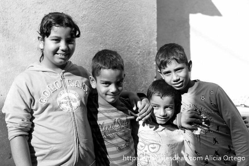 una niña y tres niños gitanos de bulgaria posando sonrientes para la foto