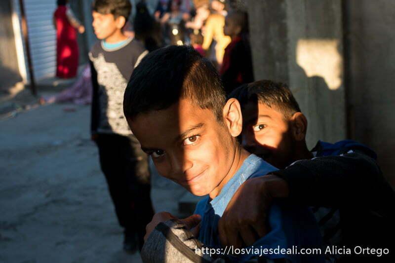 dos niños mirando a la cámara retadoramente con luz de atardecer y sombras