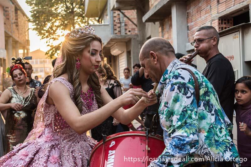 novia con vestido de princesa rosa con brillantes y corona, poniendo un billete en el cuello al que toca el tambor en su boda gitanos de bulgaria