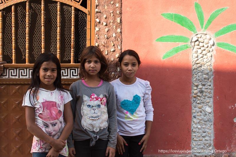 tres niñas posando junto a una pared donde hay pintada una palmera