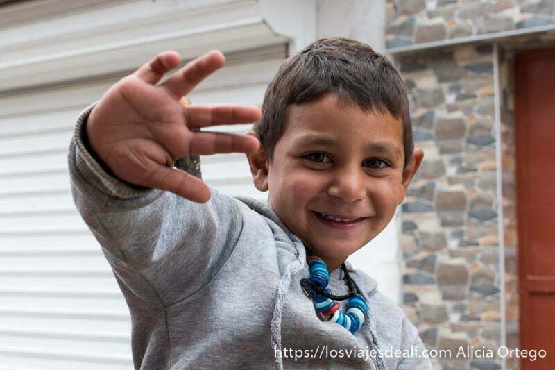 niño gitano sonriente levantando una mano y con un collar de cuentas de colores al cuello