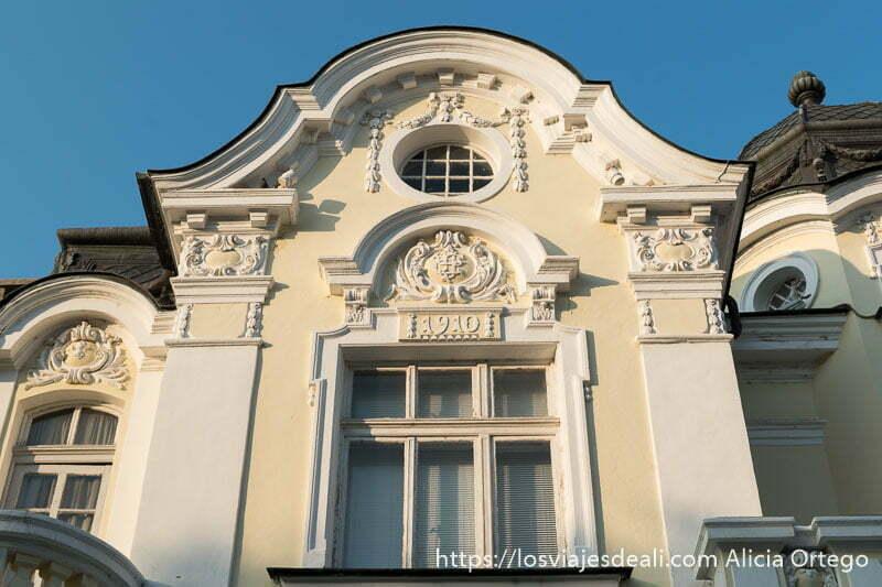 edificio clásico de sliven pintado de color crema y blanco y con una placa que pone 1910