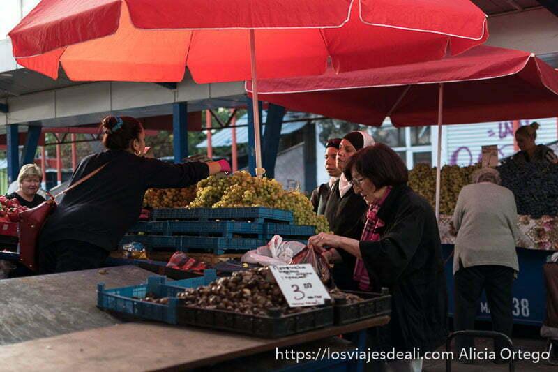 puesto de uvas y castañas con sombrilla roja y dos mujeres musulmanas comprando a la vendedora