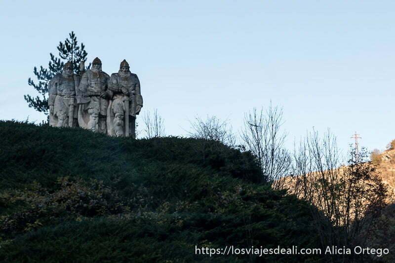 estatua de tres guerreros tracios en la ladera de un monte está hecha de piedra y aparecen con cascos, capa y espada de guerreros