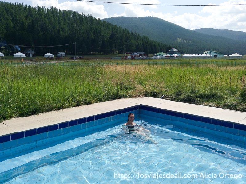 dándome un baño en la piscina de aguas termales de tsenherin y al fondo montañas llenas de bosque y otro campamento